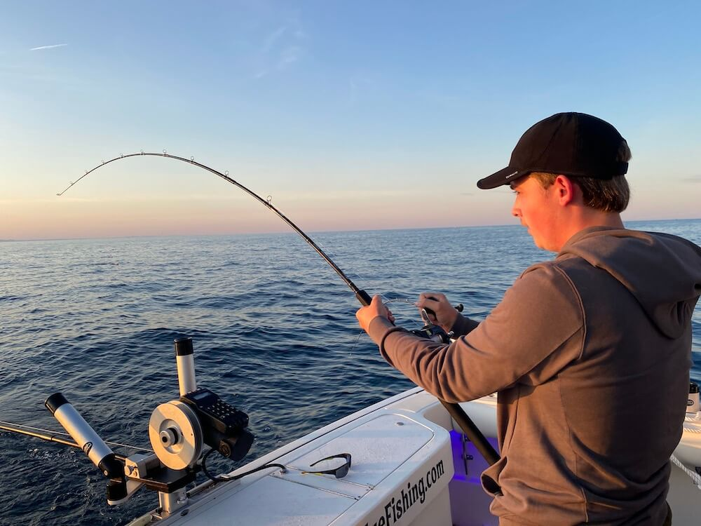 Adam Compton reeling in a 15lb Lake trout in Grand Haven on the Good Eye Fishing Vessel