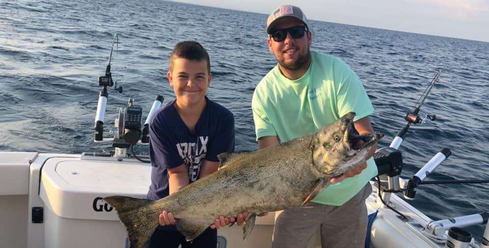 Young man and CJ Anastor with a Salmon on the Good Eye Fishing Charter